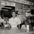 Ernest C.  Withers, A young African American woman wears a white blouse and apron and stands behind a diner counter.